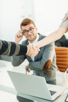 Uścisk dłoni partnerów biznesowych na tle profesjonalnego pracownika