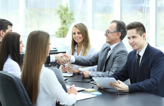 Uścisk dłoni partnerów biznesowych przy stole negocjacyjnym w biurze