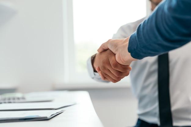 Uścisk dłoni partnerów finansowych w pobliżu pulpitu.