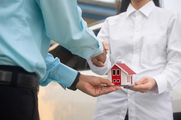 Uścisk dłoni po umowie i sprzedawca oddający dom klientowi
