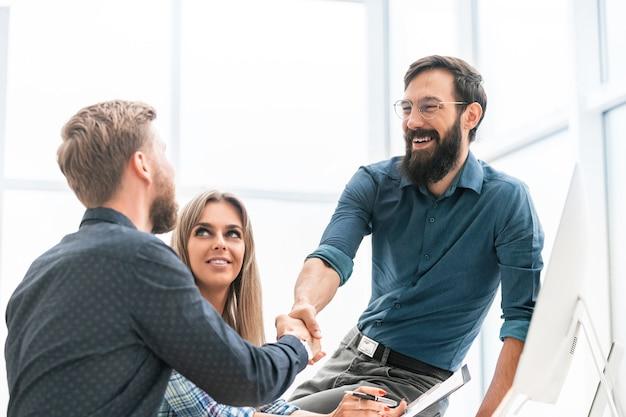 Uścisk dłoni pracowników w miejscu pracy w biurze. koncepcja sukcesu