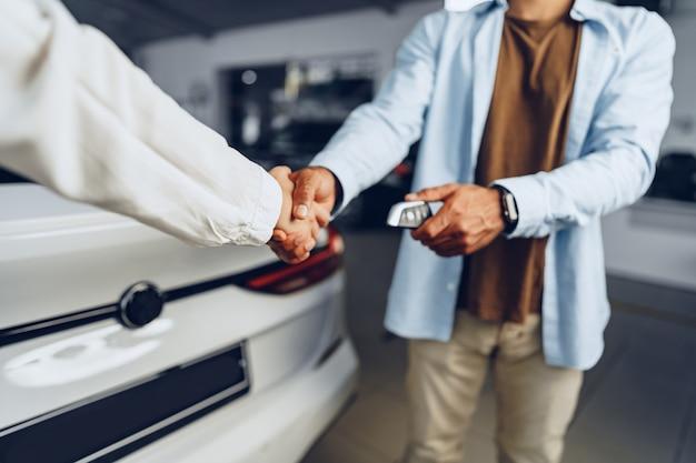 Uścisk dłoni sprzedawcy i kupującego w salonie samochodowym w stosunku do nowego samochodu