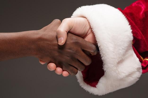 Uścisk dłoni świętego mikołaja i ręka afrykańskiego człowieka. wesołych świąt bożego narodzenia koncepcja