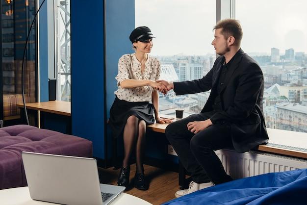 Uścisk dłoni szczęśliwego biznesmena i klienta, pracowników firmy w nowoczesnym biurze świętuje sukces