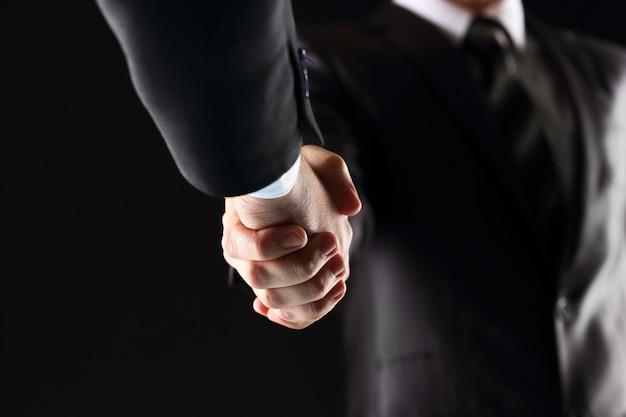 Uścisk dłoni - trzymająca dłoń na czarnym tle