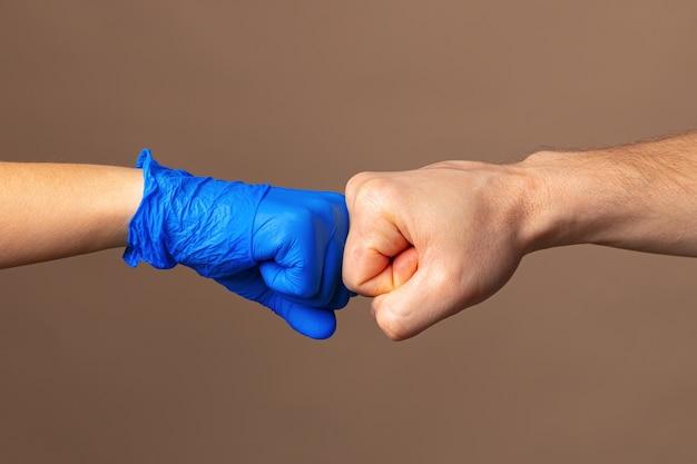 Uścisk dłoni w błękitnych rękawiczkach, pomocy pojęcie. higiena osobista podczas pandemii