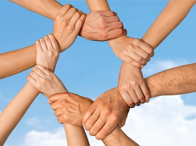 Uścisk dłoni wielu młodych ludzi biznesu, koncepcja pracy zespołowej