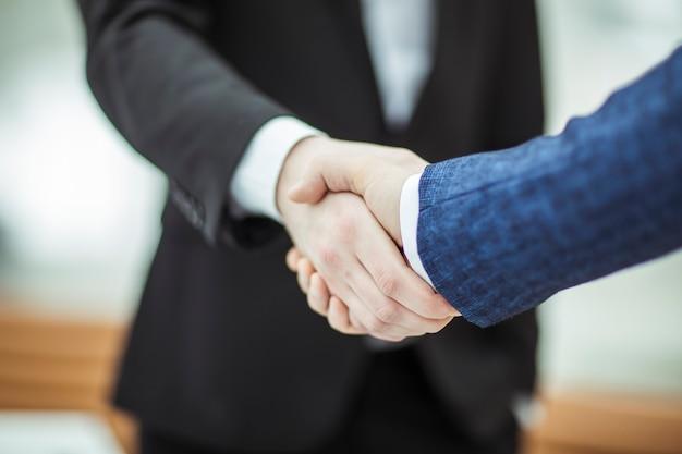 Uścisk dłoni z partnerami biznesowymi na tle jasnego biura.