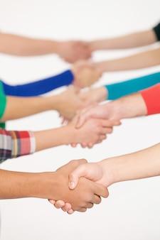 Uścisk dłoni. zbliżenie na ludzi, którzy ściskają dłonie, stojąc w rzędzie