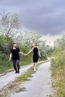 Uściski i kochająca się para w gałęziach krzaków. idź wzdłuż drogi, mężczyzna całuje kobietę. miłość, przywiązanie, związek, żywe emocje na twarzy. wschodnia kochająca para