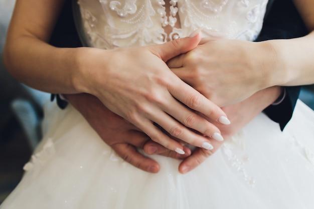 Uściski. męskie ramię wokół talii kobiety. kochankowie w ramionach. mężczyzna obejmuje dziewczynę.