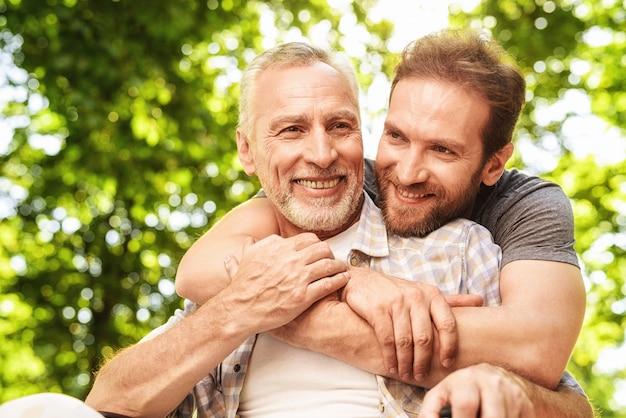 Uściski rodzinne. mężczyzna nosi ojca na wózku inwalidzkim.