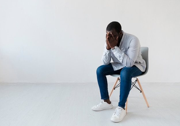 Usiadł afro amerykański mężczyzna siedzi na krześle