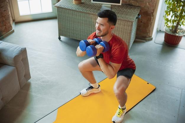 Usiądź. młody kaukaski mężczyzna trenuje w domu podczas kwarantanny epidemii koronawirusa, robi ćwiczenia fitness, aerobik. nagrywanie wideo lub przesyłanie strumieniowe online. wellness, sport, koncepcja ruchu.