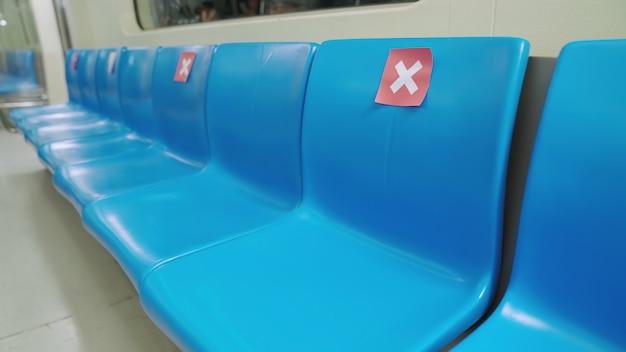 Usiądź w publicznym podziemnym metrze ze znakami ostrzegającymi o zachowaniu odległości jednego miejsca w celu ochrony przed rozprzestrzenianiem się covid-19