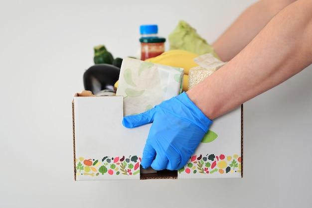 Usługa dostawy do domu podczas covid19 dostarczania świeżych warzyw i składników żywności do klienta w domudostawca w rękawiczkach ochronnych trzyma koszyk na zakupy z zakupamidostawa żywności online
