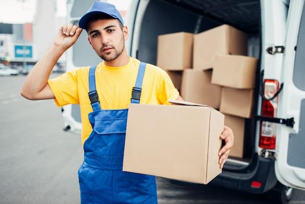 Usługa dostawy ładunków, kurier męski w mundurze z pudełkiem w dłoni i ciężarówką z paczkami kartonowymi. pusty pojemnik