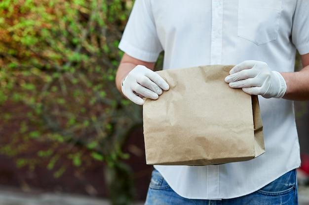 Usługa dostawy objęta kwarantanną. kurier, człowiek dostawy w lateksowych rękawiczkach medycznych bezpiecznie dostarcza zakupy online w brązowych papierowych torebkach podczas epidemii koronawirusa