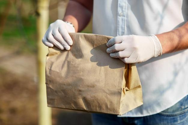 Usługa dostawy objęta kwarantanną. kurier, człowiek dostawy w medycznych lateksowych rękawiczkach bezpiecznie dostarcza zakupy online w brązowych papierowych torebkach podczas koronawirusa