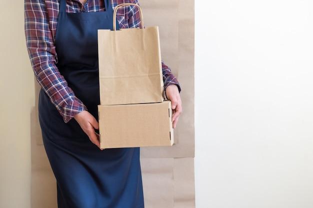 Usługa dostawy pracownik pakowanie torby pudełko fartuch pakowacz wysyłka otwarta kawa na wynos