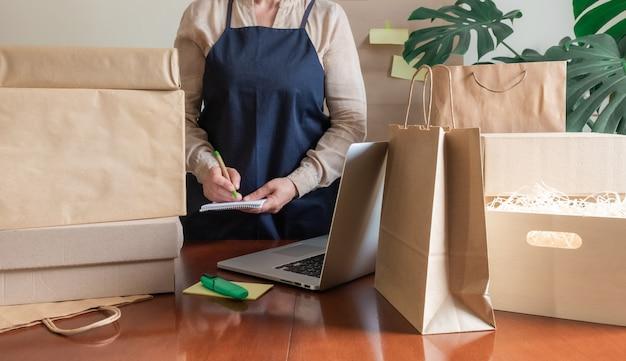 Usługa dostawy pracownik pakowanie worek pudełko laptop pc online notatka pakowacza