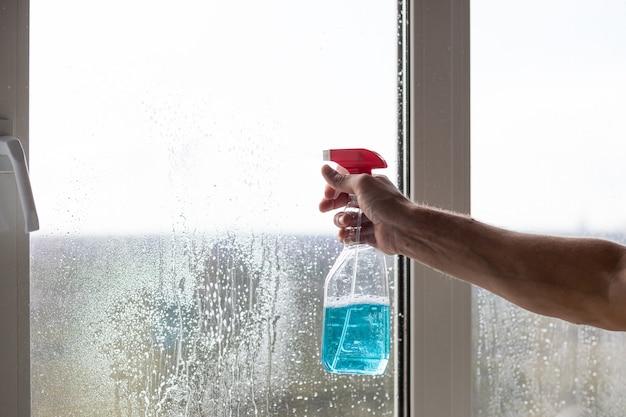 Usługa sprzątania przyszła posprzątać nowy dom. pracowity kaukaski mężczyzna starannie czyści okno. czerwone rękawiczki trzyma rozpylającą niebieską butelkę na oknie. czyszczenie okien specjalną szmatką i środkiem czyszczącym