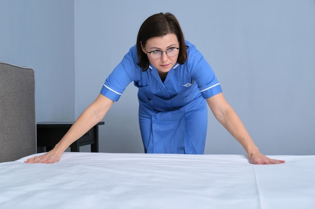 Usługa sprzątania w pokoju hotelowym, kobieta w średnim wieku profesjonalna pokojówka przygotowująca ścielenie łóżka, miejsce na kopię