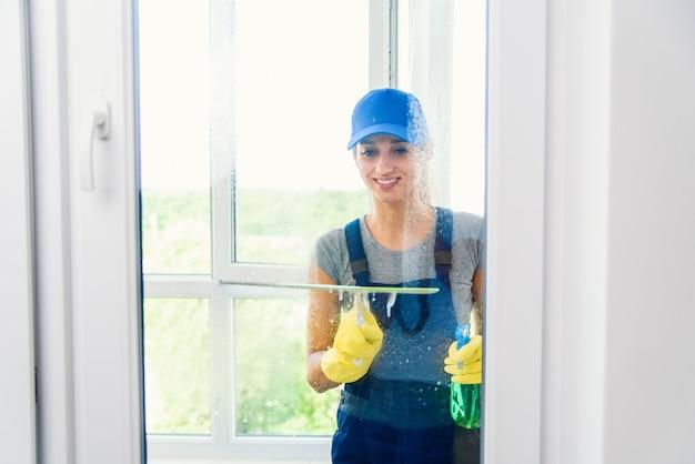 Usługa sprzątania z profesjonalnym sprzętem podczas pracy. profesjonalne czyszczenie dywanów, czyszczenie na sucho sof, mycie okien i podłóg. kobiety w mundurach, kombinezonach i gumowych rękawiczkach.