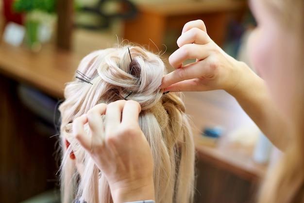 Usługi fryzjerskie. stworzenie fryzury wieczorowej. proces układania włosów.
