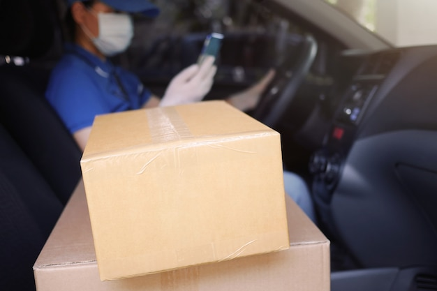 Usługi kurierskie podczas pandemii koronawirusa (covid-19), kartonowe pudła na siedzeniu samochodu dostawczego z kierowcą kuriera w niewyraźnej masce medycznej i lateksowych rękawiczkach z telefonem
