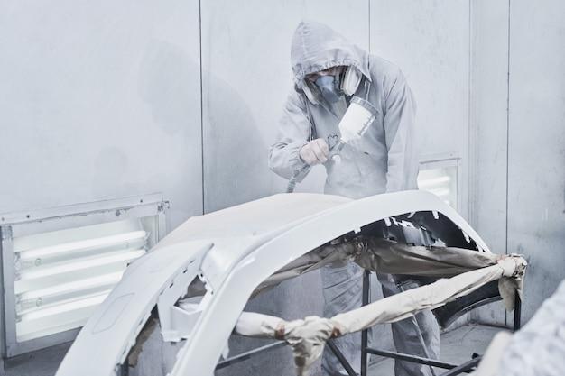 Usługi malowania i naprawy samochodów. mechanik samochodowy w białym kombinezonie maluje samochód za pomocą rozpylacza aerografu w komorze lakierniczej