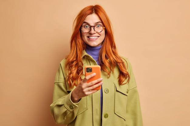 Usługi mobilne i koncepcja komunikacji online. zadowolona piękna rudowłosa młoda kobieta trzyma nowoczesny telefon komórkowy uśmiecha się zębato ubrana w modną jesienną marynarkę.
