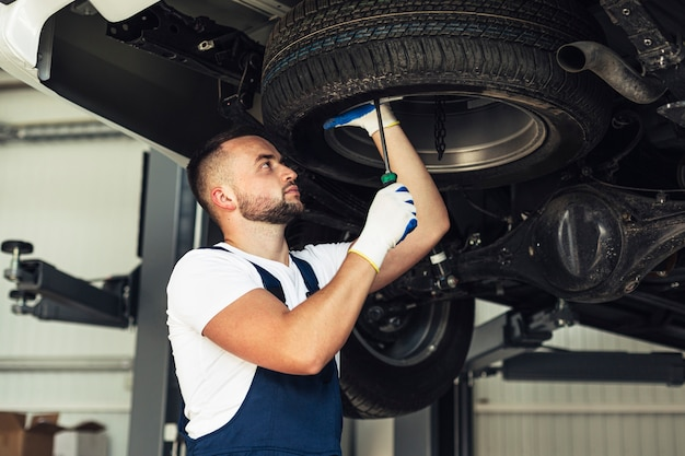 Usługowy samochodowy męski pracownik sprawdza samochodowych koła