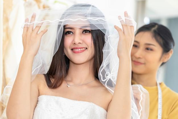 Uśmiech azjatycka kobieta mierzy na ślubnej sukni w sklepie krawczyną.