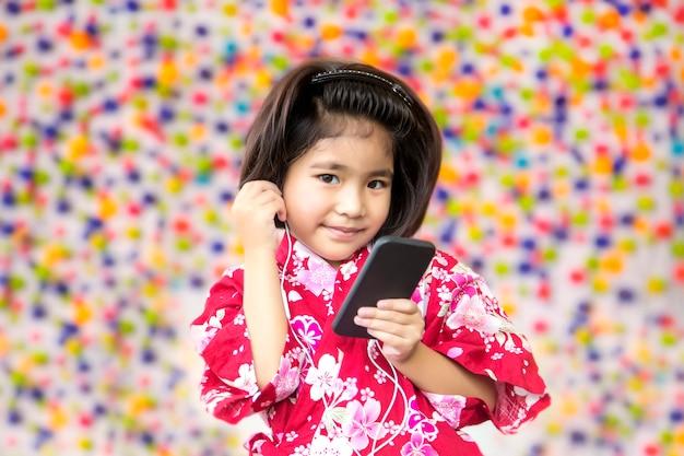 Uśmiech azjatycki dziewczyna ze słuchawek i telefonu komórkowego
