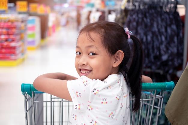 Uśmiech azjatykcia mała dziewczynka w wózek na zakupy przy sklepem spożywczym