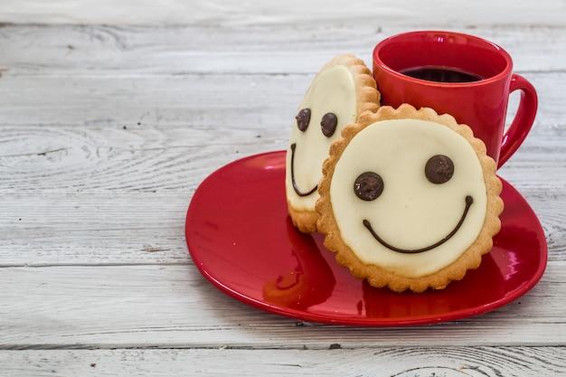 Uśmiech ciasteczka na czerwonym talerzu z filiżanką kawy, drewnianą ścianą, jedzeniem