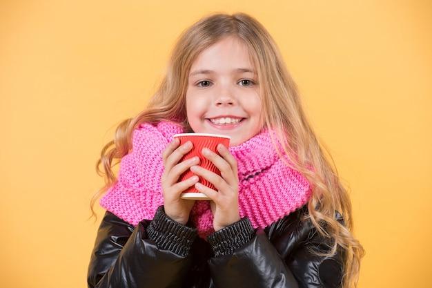 Uśmiech dziecka z czerwonym kubkiem na pomarańczowym tle. herbata lub kawa na wynos. koncepcja sezonu jesiennego. dziewczyna z długimi blond włosami w czarnej kurtce trzymać kubek. rozgrzej napój.