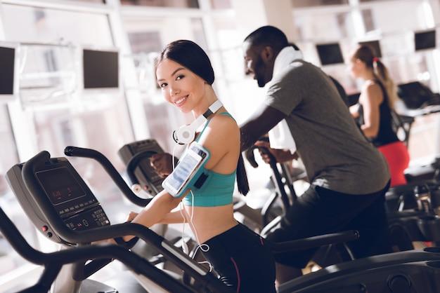 Uśmiech dziewczyna w siłowni koncentruje się na bieganie