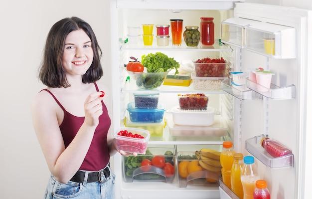 Uśmiech dziewczyna z jagodami w pobliżu lodówki ze zdrową żywnością
