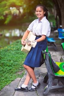 Uśmiech dziewczyny ucznia mienie i bawić się gitara.