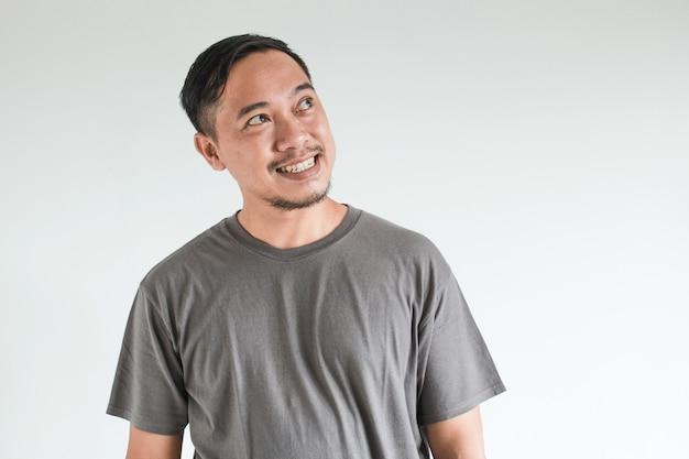 Uśmiech i szczęśliwy wyraz twarzy azjatyckiego mężczyzny wskazują pustą przestrzeń treści koncepcja modelu reklamowego