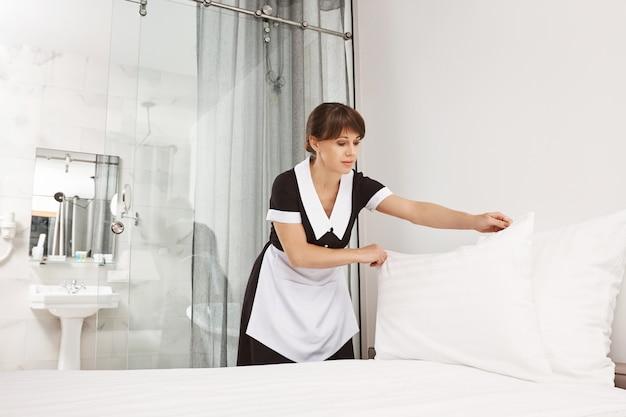 Uśmiech klienta sprawia, że czuję się lepiej. kobieta w mundurze pokojówki pościeli łóżko w sypialni, wkładając poduszkę po wcześniejszym umyciu. pokojówka próbuje zakończyć sprzątanie, zanim właściciele domu wrócą