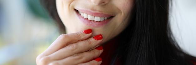 Uśmiech kobiety i palce z czerwonymi paznokciami