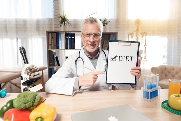 Uśmiech lekarz trzyma znak diety w pokoju kliniki.