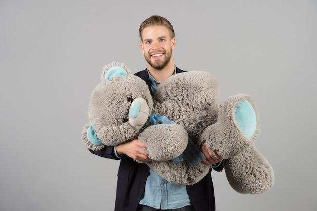Uśmiech macho z szarym misiem szczęśliwy człowiek duża zabawka dla zwierząt uśmiech mężczyzny z dużą zabawką dla zwierząt prezent