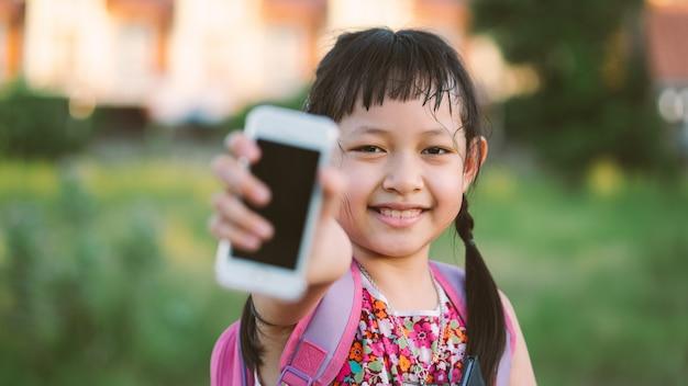 Uśmiech małej szkolnej dziewczyny mienia smartphone i książka z plecakiem. tylna koncepcji do szkoły