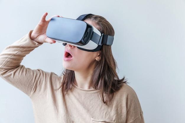 Uśmiech młoda kobieta jest ubranym używać rzeczywistości wirtualnej vr szkieł hełma słuchawki na białym tle. używanie smartfona z goglami wirtualnej rzeczywistości. technologia, symulacja, hi-tech, koncepcja gier wideo.
