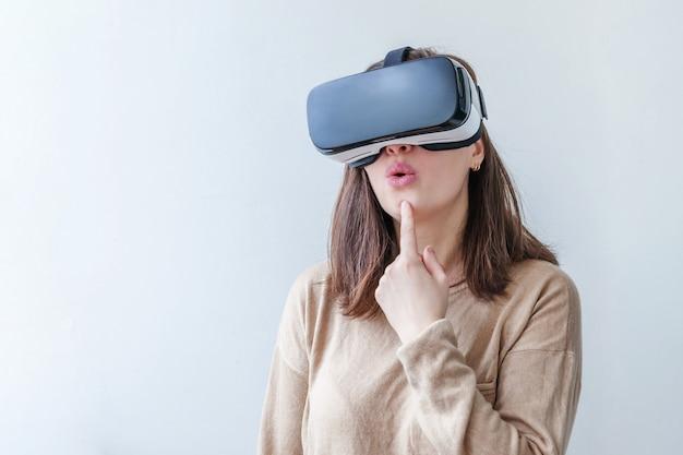 Uśmiech młoda kobieta jest ubranym używać rzeczywistości wirtualnej vr szkieł hełma słuchawki na bielu. używanie smartfona z goglami wirtualnej rzeczywistości. technologia, symulacja, hi-tech, koncepcja gier wideo