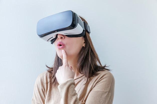 Uśmiech młoda kobieta ubrana za pomocą zestawu słuchawkowego kask okulary wirtualnej rzeczywistości vr na białym tle.